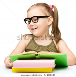 Cute little girl is reading a book while wearing glasses, isolated ...