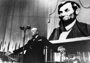 Winston Churchill speaking in front of a portrait of Abraham Lincoln