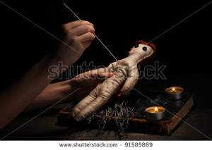 Voodoo doll girl pierced by a needle on a wooden table in the ...
